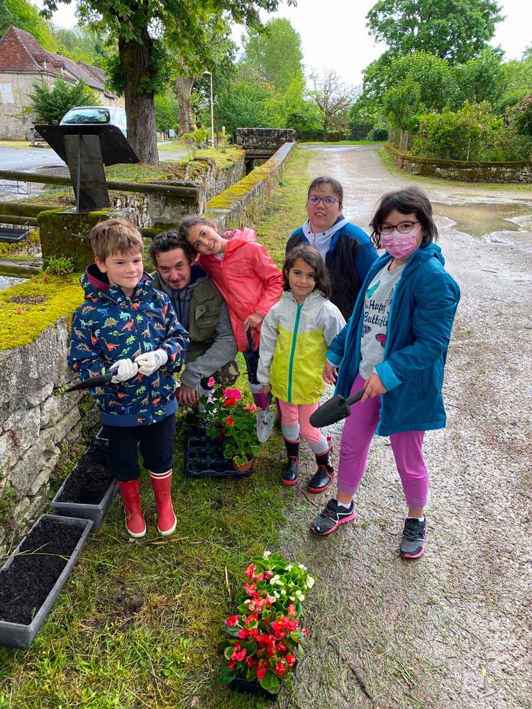 photos des enfants et des conseillers qui fleurissent le village